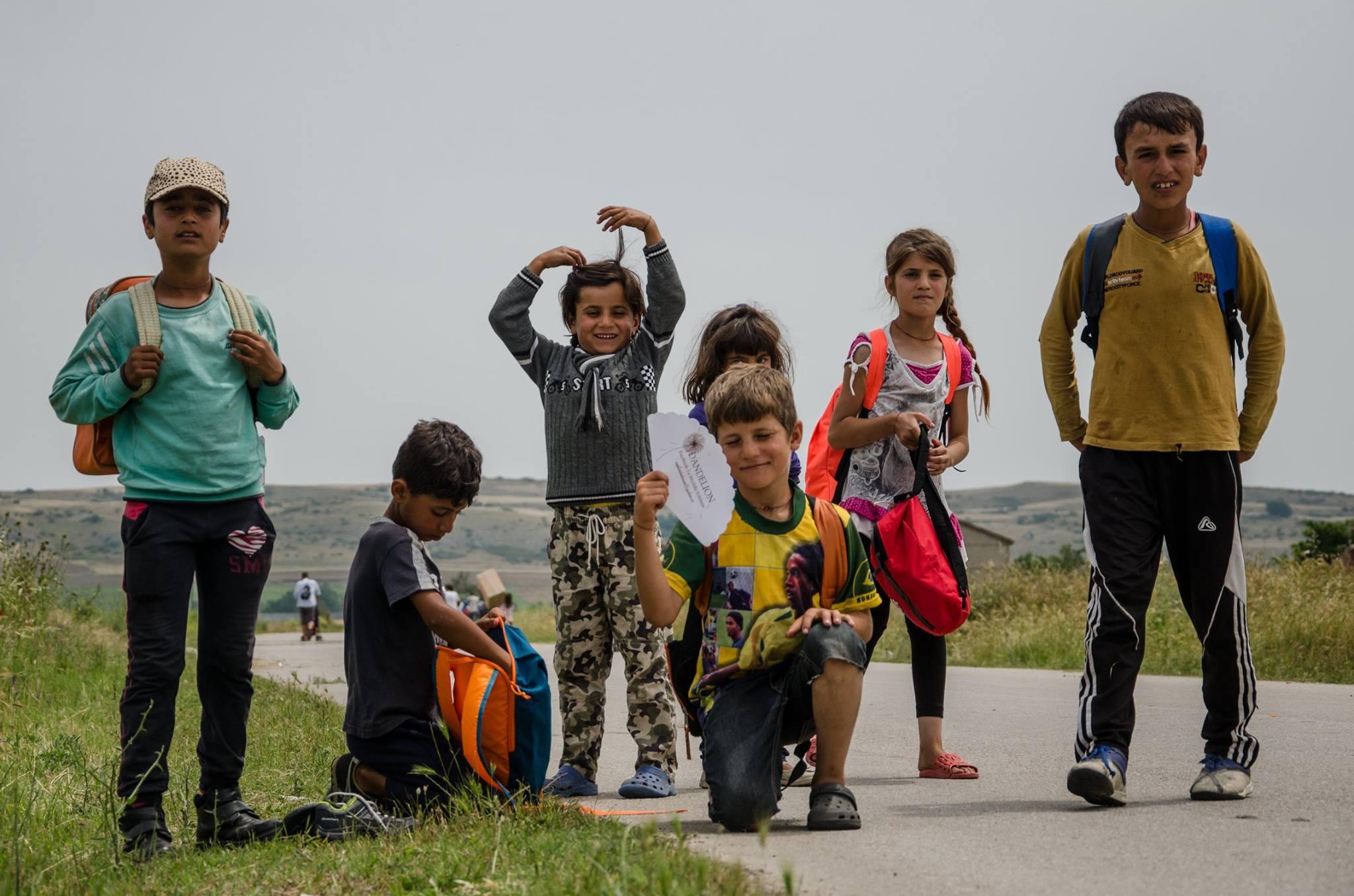 Niños contentos con sus mochilas en el campamento de Nea Kavala